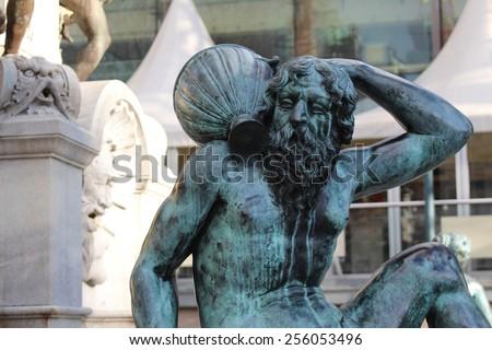 INNSBRUCK, AUSTRIA - DECEMBER 25: Statue of a man carrying a demijohn on  Rennweg on December 25, 2014 in Innsbruck. The statue is a part of a fountain near Tiroler Landestheater. - stock photo
