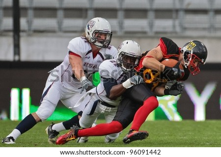 INNSBRUCK, AUSTRIA - JULY 10 WR Niklas R?mer (#84 Germany) is tackled at the Football World Championship on July 10, 2011 in Innsbruck, Austria. USA wins 48:7 against Germany. - stock photo