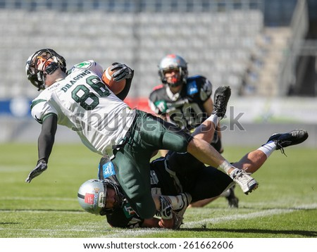 INNSBRUCK, AUSTRIA - MARCH 29, 2014: WR Georg Pongratz (#86 Dragons) is tackled by LB Stefan Werner (#46 Raiders) in an AFL football game. - stock photo