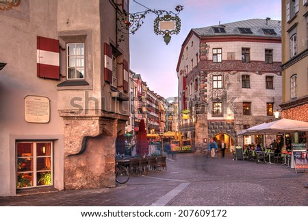 INNSBRUCK, AUSTRIA - OCTOBER 11: Evening scene in downtown Innsbruck, Austria along the Herzog-Friedrich street on Oct 11, 2011, featuring some of the historical houses and the animated atmosphere. - stock photo