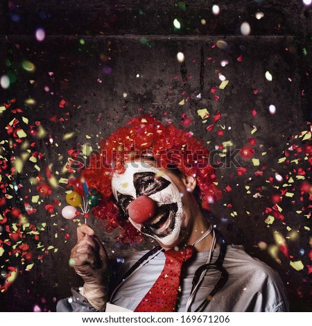 Insane circus clown with smile holding miniature balloons under falling confetti during a birthday party celebration at a hospital ward - stock photo