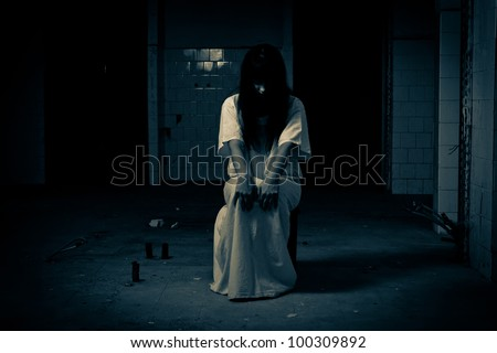 Insane woman sitting on chair in  a white dress - stock photo