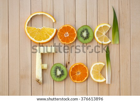 inscription from tropical fruit good food, letters of sliced fruit on a wooden surface, the original lettering of citrus, orange, pineapple, kiwi, lemon, tangerine on wooden boards, closeup, flat lay - stock photo