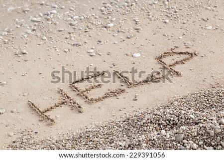 """Inscription """"Help"""" on sandy beach  - stock photo"""