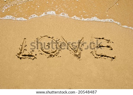 inscription Love on a sand at sunny day