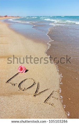 Inscription love on the wet sand of the sea, beach in a quiet cove of the Mediterranean Sea and  flower of  rose - stock photo