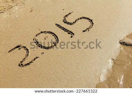 inscription New 2015 Year on the sand and wave near - stock photo