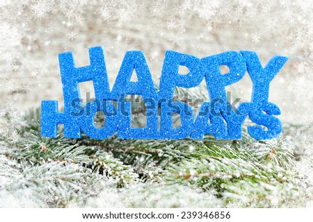 Inscription of happy holidays with spruce branches with frost - stock photo