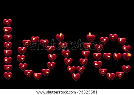 inscription of love candles on a black background - stock photo