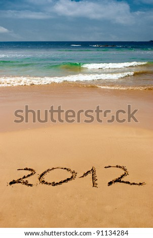 inscription 2012 on a beach sand in front of the ocean - stock photo
