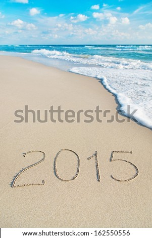 inscription 2015 on sea sand beach with the sun rays against wave foam and sky - vacation concept - stock photo