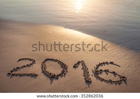 Inscription 2016 on sea sand beach with the sun rays against wave foam. Vacation concept - stock photo