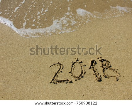 inscription 2018 on the sand