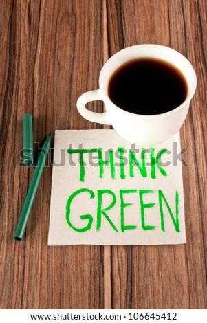 Inscription Think Green on a napkin and cup of coffee - stock photo