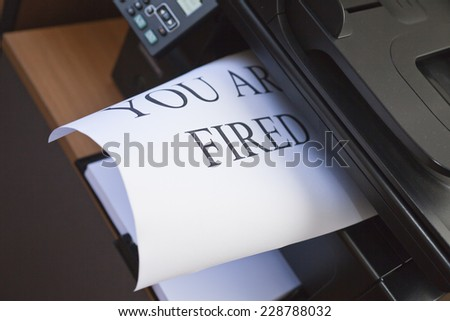 "Inscription ""You are fired"" on the sheet of white paper"