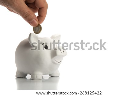 Insert coin in a happy piggy bank. Isolated on white, selective focus on coin. - stock photo