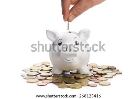 Insert coin in a smiling piggy bank,  selective focus - stock photo