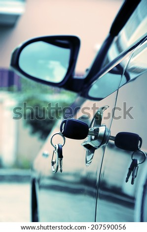 Insert the car key in the door of the car. - stock photo