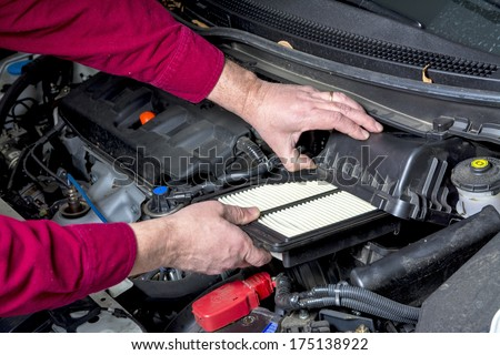 Inserting a fresh air filter in cars engine - stock photo