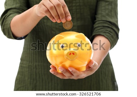 Inserting coin in a piggy bank - stock photo