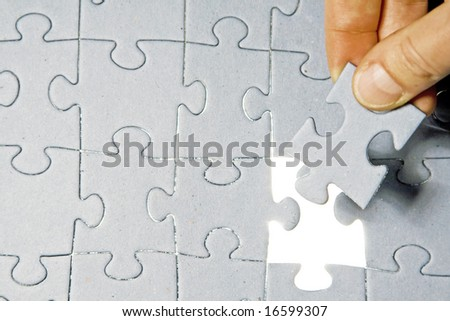 Inserting last piece of puzzle - stock photo