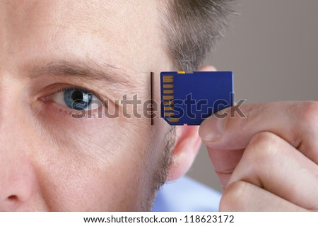 Inserting SD memory card into slot in human head concept for memory upgrade, forgetfulness or computing - stock photo