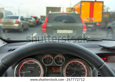 Inside a car: steering wheel of a car and motion blurred asphalt road and vehicles in a traffic jam street - stock photo