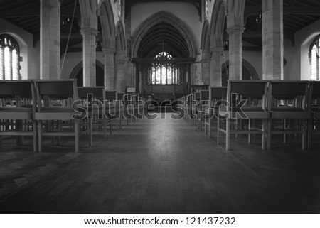 inside a church in england, view from the back looking down to the altar - stock photo