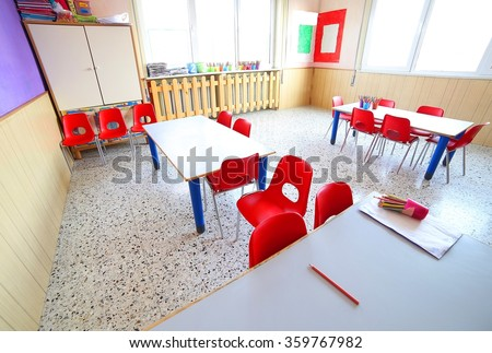 inside a classroom with school desks and small red chairs - stock photo