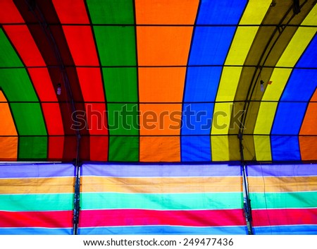 Inside a colorful tent. The tent consists of green, red, orange, blue, yellow and purple colors and lines form repetitive patters of color strips. There are lamps hanging down the tent props.
