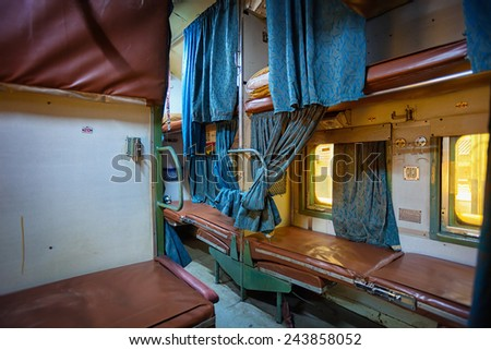 Inside a grungy and uncomfortable passenger car aboard a train in India. - stock photo
