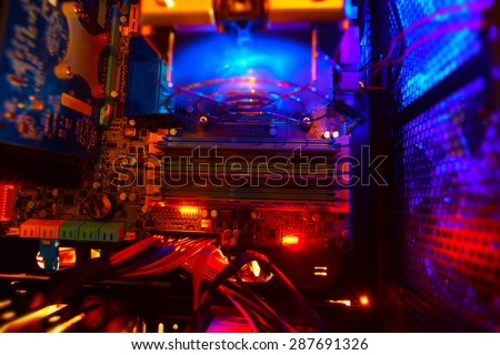 Inside a high performance computer. Computer circuit board and CPU cooling fans illuminated by internal LEDs inside a server class computer. - stock photo