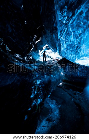 Inside an icecave in Vatnajokull, Iceland. A climber silhoutted against the ice. The ice is thousands of years old and so packed it is harder than steel and crystal clear. - stock photo