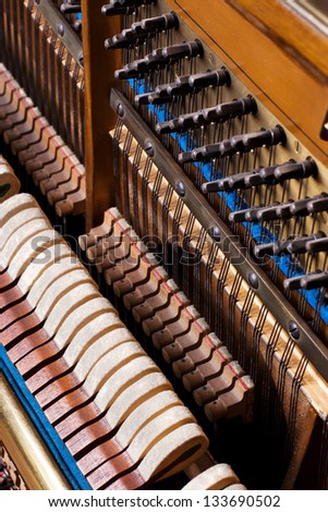 Inside an Upright Piano. Felt Hammers used to strike Steel Strings and wound knobs to tune. - stock photo