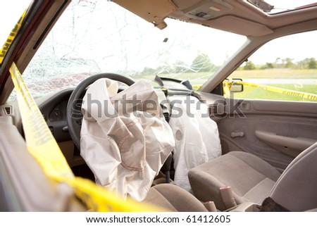 Inside Automobile After Wreck.  Driver and Passenger Air Bags Deployed.  Windshield Shattered with yellow police tape around the vehicle. - stock photo