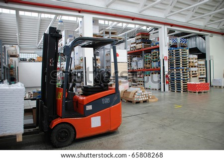 Inside of factory warehouse with forklift and goods - stock photo