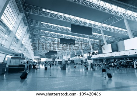 inside the airport terminal with passenger motion blur - stock photo