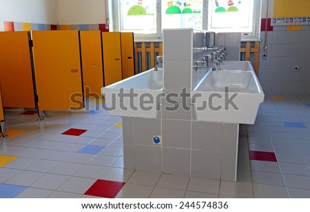 inside the bathroom of the nursery school with white sinks and doors yellow - stock photo