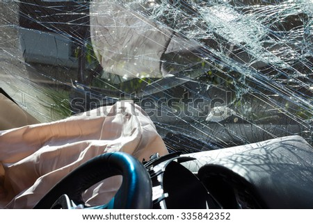 Inside the car, sunny, with airbags and windshield cracks due to accident damage. - stock photo