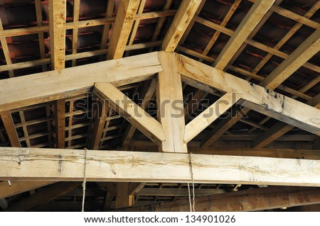 inside the roof structure with wooden beams traditional style - stock photo