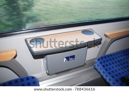 Inside the train carriage, Germany. Empty train seats next to the window with a small table and a garbage container. Translation of the sign: A large waste container is in the anteroom