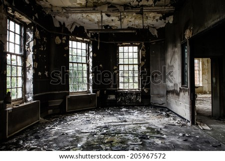 inside view of a deserted run down building after a fire - stock photo