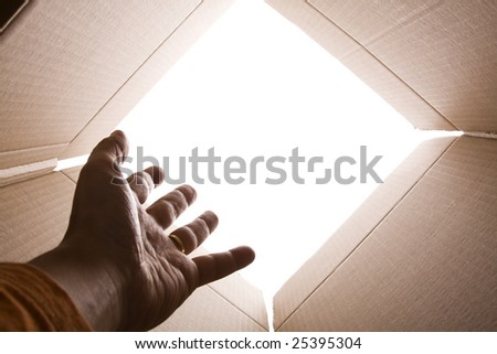 inside view of cardboard box with a hand trying escape (selective focus) - stock photo