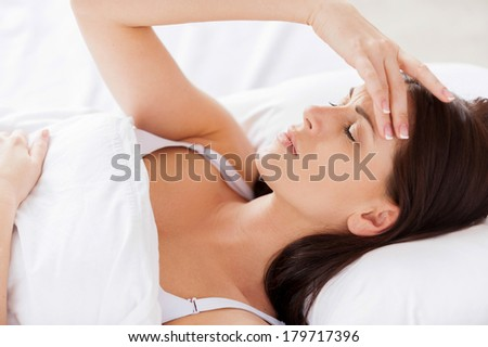 Insomnia. Attractive young woman holding hand in hair and keeping eyes closed while lying in bed