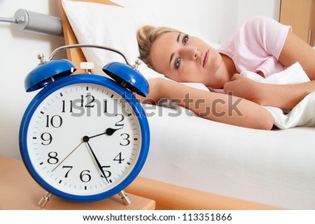insomnia with clock in the night. woman can not sleep. - stock photo