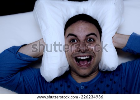Insomniac man using a pillow to cover his ears - stock photo