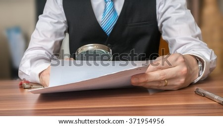 Inspection of document with magnifying glass. Layer is analysing contract. - stock photo