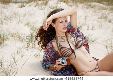 Inspiration captured on wild and wonderful beaches. Bohemian young woman with retro photo camera laying on a white beach and looking into the distance