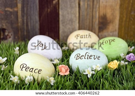 inspirational message on pastel colored Easter eggs in grass with flowers - stock photo