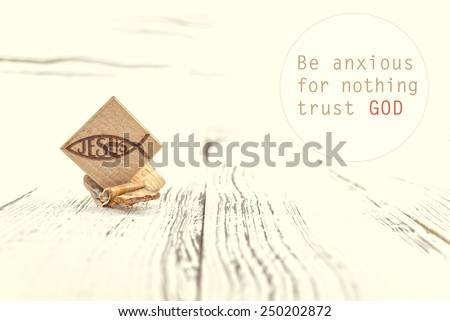 Inspirational motivating quote saying that God has everything in control. Christian fish symbol carved in wood on white vintage wooden background - stock photo